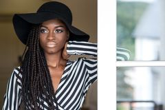 Beautiful young african american girl with dreadlocks or african braids wearing big black hat. royalty free stock image