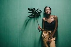 Beautiful young african american girl posing on green wall. Fash stock photo