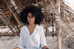 Beautiful young african american girl sitting on sand at the bea Royalty Free Stock Photos