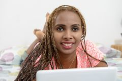 Beautiful young african american woman with braids using a table Stock Image