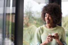 African American woman drinking coffee looking out the window. Beautiful young african american woman drinking coffee and looking through a window in her luxury Royalty Free Stock Photo