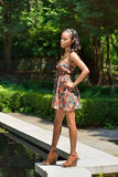 Beautiful young African American woman in floral sundress. Stunning young African-American woman standing next to a small fountain in an outdoor garden Stock Photos