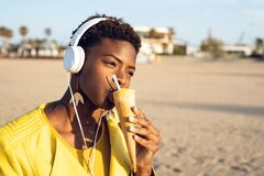 Beautiful young African American woman happy eating ice cream stock image