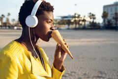 Beautiful young African American woman happy eating ice cream stock photography