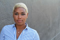 Beautiful young African American woman with short dyed blond hair looking at camera with a relaxed neutral expression.  royalty free stock photography
