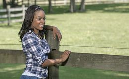 Beautiful young African American woman standing along farm fence - rural Royalty Free Stock Photos