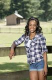 Beautiful young African American woman standing along farm fence - rural Stock Photography