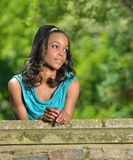 Beautiful young African American woman standing along stone wall Royalty Free Stock Photos