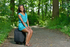 Beautiful young African American woman with suitcase on road Royalty Free Stock Photo