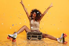 Beautiful young african woman with afro hairstyle throwing confetti, showing peace gesture while sitting in roller skates with bo. Ombox, isolated on yellow royalty free stock image