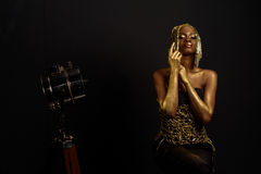 Beautiful young african woman in gold clothes and accessories posing at studio, face with hand portrait over dark background Stock Photography