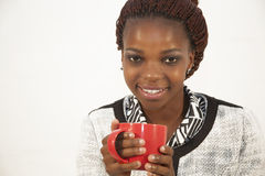 Beautiful young african woman holding a cup of coffee Stock Images