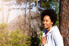 Beautiful young african woman leaning on tree trunk Royalty Free Stock Photos