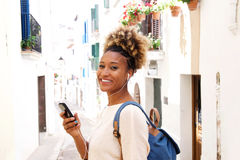 Beautiful young african woman listening music with earphones on narrow street Stock Images