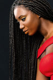 Beautiful young african woman with long braided hair. Close up vertical beauty portrait of young african woman with long braided hair against dark background Stock Photos