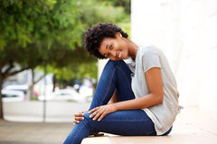 Beautiful young african woman sitting by a city street Royalty Free Stock Photography