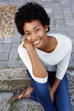 Beautiful young african woman sitting outside Royalty Free Stock Photography