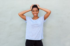 Beautiful young african woman smiling with hands behind head Stock Photos