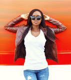 Beautiful young african woman in sunglasses and jacket at city over red Royalty Free Stock Photos