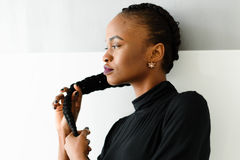 Beautiful young african woman touching her long hair on studio background Royalty Free Stock Photo