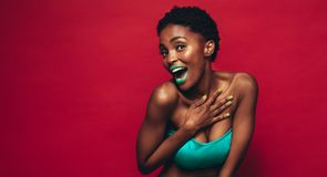 Beautiful young african woman with vivid makeup. Against red background. Cheerful female model wearing artistic makeup looking at camera Royalty Free Stock Photos