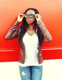 Beautiful young african woman wearing a jacket, sunglasses in city over red Royalty Free Stock Image