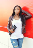 Beautiful young african woman wearing a leather jacket with handbag clutch Royalty Free Stock Photo