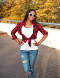 Beautiful young african woman wearing sunglasses and red checkered shirt in city. Beautiful young african woman wearing a sunglasses and red checkered shirt in Royalty Free Stock Photo