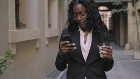 Confident business woman walks street. Beautiful young afro american black woman with long black hair and glasses,wears casual professional business outfit on stock footage