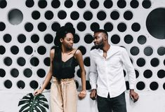 Attractive couple in matching clothes smiling at camera on white. Beautiful young Afro American couple is looking at camera and smiling, on gray background Royalty Free Stock Photo
