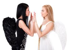 Beautiful young angel playing pat-a-cake with a black angel isol Stock Photos