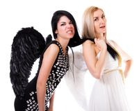 Beautiful young angel pulls black angel's hair Stock Image
