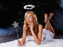 Beautiful young angel woman lying in snowfall Royalty Free Stock Photos