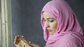 Beautiful young arabian woman standing by a window and talking on cell phone.  stock video