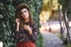 Beautiful young arabic woman with black curly hairstyle. Arab girl wearing casual clothes in the street Royalty Free Stock Images