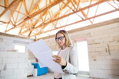 Architect at the construction site looking at blueprints. Royalty Free Stock Photography
