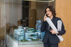 beautiful young architect with rolled building plans talking royalty free stock photography