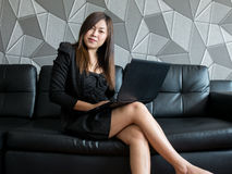 Beautiful young asia business woman sitting on sofa, working with laptop computer and wear black suit watching to camera and smile Stock Photos