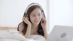 Beautiful young asia woman lying in bedroom using laptop computer relax listen music, girl showing video call chat at home stock video footage