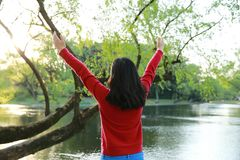 Beautiful young Asian Chinese girl hug in nature in spring autumn park. Lovly young woman hug nature in a spring autumn park, stand by a river, careless woman Stock Photography