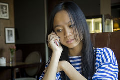 Beautiful young Asian girl in cafe. Portrait of the beautiful young Asian girl in cafe with a mobile phone royalty free stock image