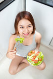 Beautiful young asian girl eating salad. smiling happy girl eati Royalty Free Stock Photo