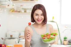 Beautiful young asian girl eating salad. smiling happy girl eati Stock Image