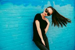 Beautiful young asian girl with long hair wearing sunglasses and black t-shirt posing in front of blue wall. Royalty Free Stock Image