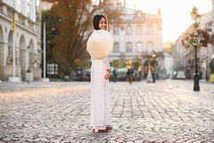 Beautiful young asian girl in national traditional Ao Dai white dress with vietnamese conical hat Non La, Leaf Hat. Asian girl walks on the street at sunrise stock photo