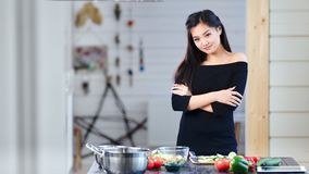Beautiful young Asian girl standing with crossed hands during cooking looking at camera stock footage