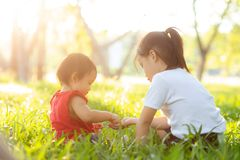 Beautiful young asian kid sitting playing in summer in the park with enjoy and cheerful on green grass. Children activity with relax and happiness together on stock image