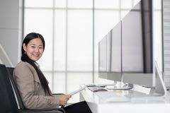 Beautiful young Asian Sitting in modern office happily, there a stock images