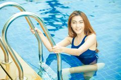 Beautiful young asian sport woman smiling getting out of swimmin Stock Image
