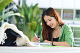 Beautiful young asian student is reading and writing Stock Image